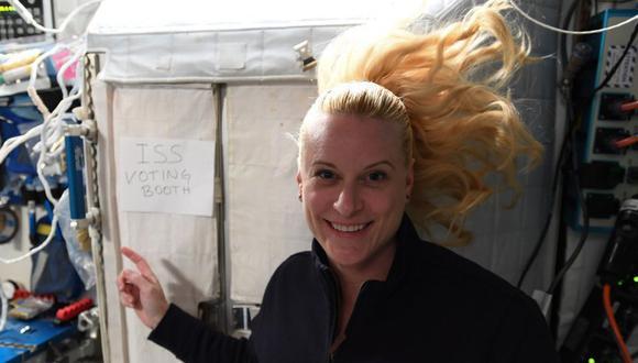 """Esta foto del 22 de octubre de 2020 muestra a Kate Rubins, astronauta de la Estación Espacial Internacional (ISS), señalando un letrero que dice """"cabina de votación de la ISS"""". (AFP)."""
