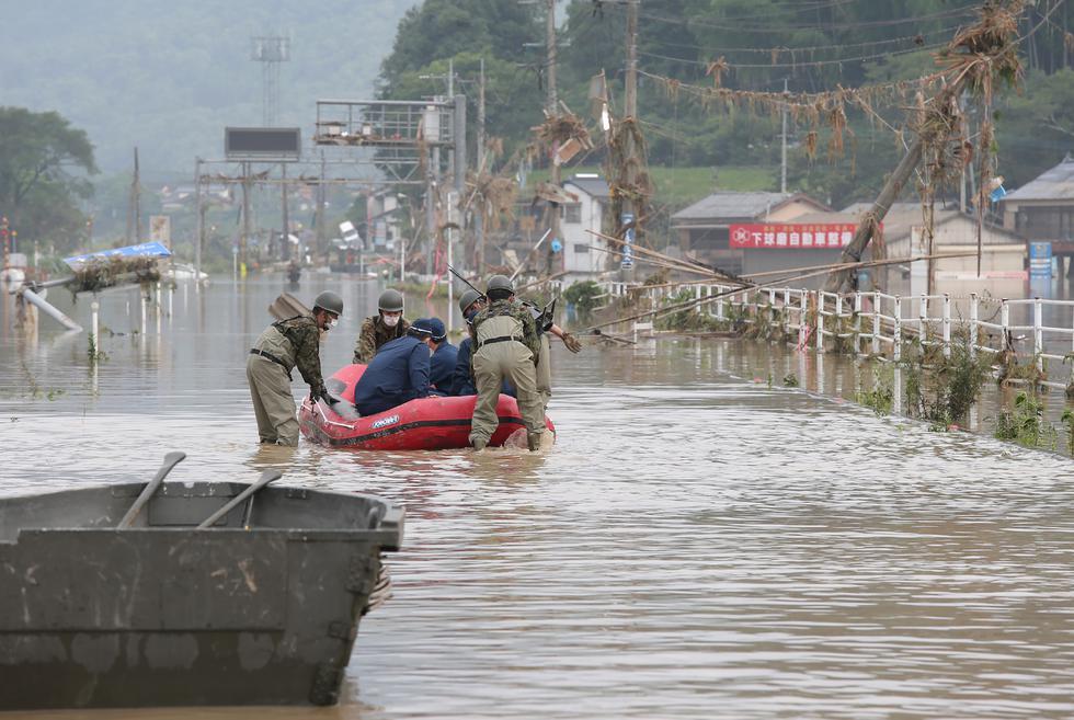 Las Fuerzas de Autodefensa de Japón y los oficiales de policía manejan un bote inflable para unirse a las operaciones de rescate en un hogar de ancianos después de las fuertes lluvias en la aldea de Kuma, prefectura de Kumamoto. (Foto: STR / JIJI PRESS / AFP)