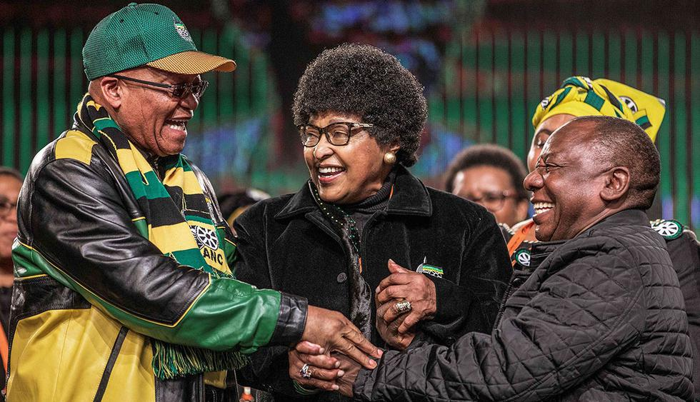 (FILES) In this file photo taken on June 30, 2017 former wife of the late South African President Nelson Mandela, Winnie Mandela (C) holds the hands of South African President Jacob Zuma (L) and South African Deputy President Cyril Ramaphosa (R) during the opening session of the South African ruling party African National Congress policy conference in Johannesburg.  Winnie Mandela, the ex-wife of South African anti-apartheid fighter and former president Nelson Mandela, died on April 2, 2018 in a Johannesburg hospital after a long illness at the age of 81, her spokesman Victor Dlamini said in a statement. / AFP / GIANLUIGI GUERCIA