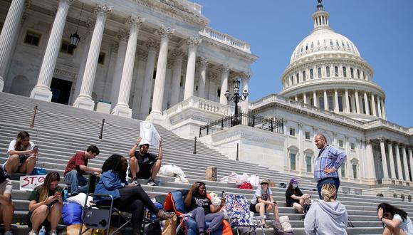 La representante estadounidense Cori Bush (al centro) sostiene su teléfono mientras transmite en vivo desde las escaleras del Capitolio en las que pasó la madrugada del sábado en protesta contra el vencimiento de la moratoria federal relacionada con la pandemia de COVID-19. (Foto: REUTERS / Elizabeth Frantz)