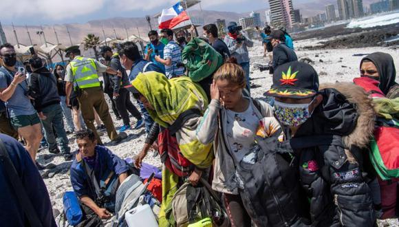 Migrantes venezolanos se refugian a la orilla del mar para evitar ser atacados por manifestantes durante una marcha de protesta contra la migración ilegal en Iquique, Chile. (Foto: MARTIN BERNETTI / AFP).