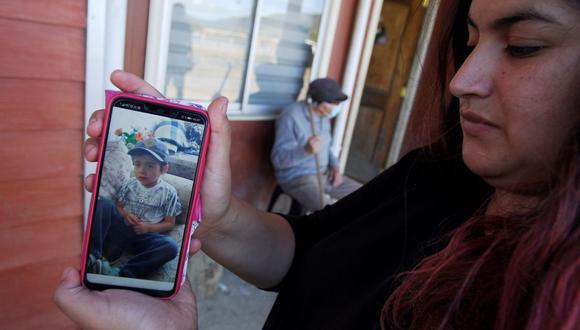 Una mujer muestra una foto del niño de tres años Tomás Bravo, quien desapareció el 17 de febrero cuando salió con un tío en busca de animales, según los informes, en la zona rural de Caripilun, Arauco, Chile. (REUTERS/Jose Luis Saavedra).