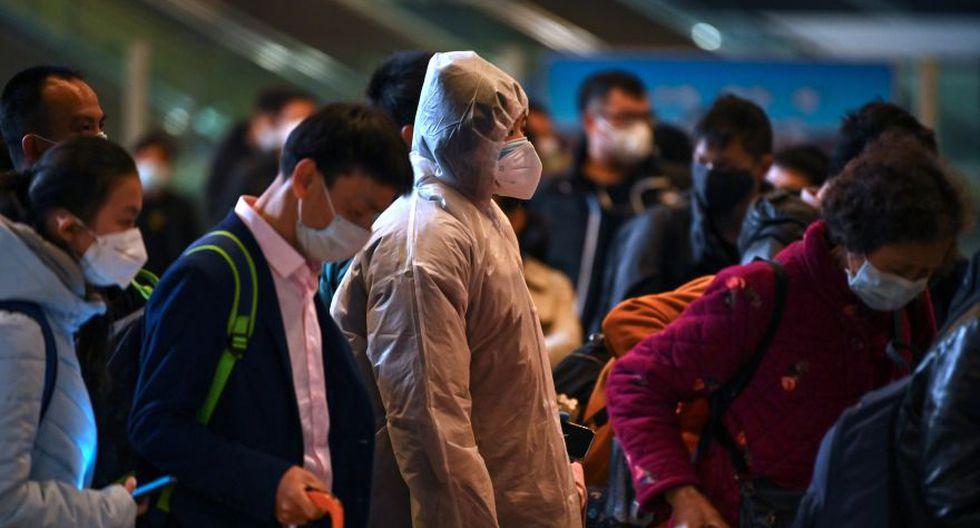 Los pasajeros esperan en una fila después de llegar a la estación de ferrocarril en Wuhan. (AFP)
