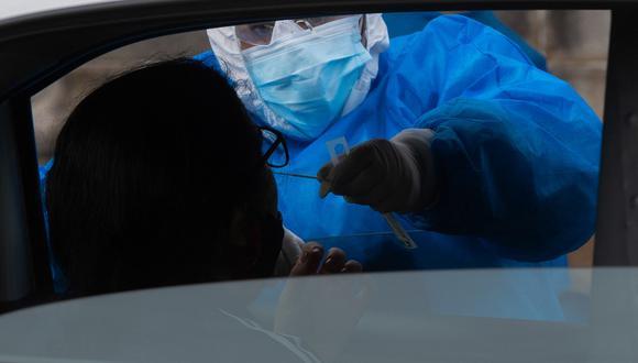 Una persona se somete a una prueba de PCR para COVID-19 en una instalación de pruebas instalada frente al Congreso de Uruguay. El Senado uruguayo aprobó el pasado viernes un proyecto de ley para limitar el derecho de reunión, luego de un repunte en el número de casos de COVID-19. (Foto: Pablo PORCIUNCULA / AFP)