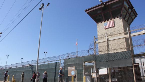 Personas pasan frente a una torre de vigilancia frente a la cerca del Campo 5 de la Prisión Militar de los Estados Unidos en la Bahía de Guantánamo, en Cuba, el pasado 26 de enero de 2017. (Thomas WATKINS / AFP).