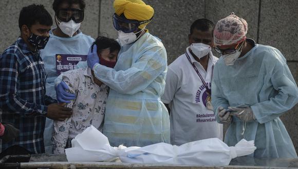 Fotografía tomada el pasado 12 de mayo de 2021, donde se muestra a un voluntario consolando a un familiar de un menor que murió debido al coronavirus en Nueva Delhi. (Arun SANKAR / AFP).