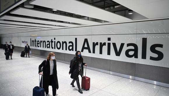 Pasajeros utilizan máscaras faciales como medida de precaución contra el COVID-19 en la sala de llegadas en el aeropuerto de Heathrow, en el oeste de Londres, el pasado 15 de enero de 2021. (DANIEL LEAL-OLIVAS / AFP)