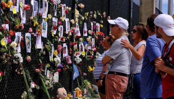 La gente llora en el lugar de conmemoración creado por los vecinos frente al edificio Champlain Towers, donde el personal de rescate continúa la búsqueda de víctimas, en Surfside, cerca de Miami Beach, Florida. (Foto: Reuters / Maria Alejandra Cardona)