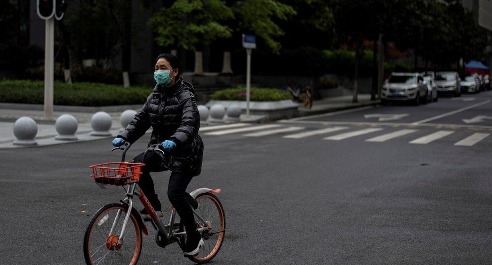 Una mujer con una máscara facial es vista en bicicleta este 28 de marzo de 2020 por una calle de Wuhan, provincia central de Hubei de China. (AFP)