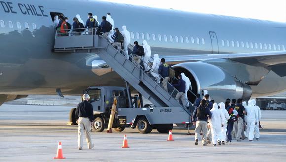 Migrantes venezolanos abordan un avión para ser deportados de Chile luego de cruzar ilegalmente por la frontera por Bolivia. (Foto de IGNACIO MUNOZ / AFP).