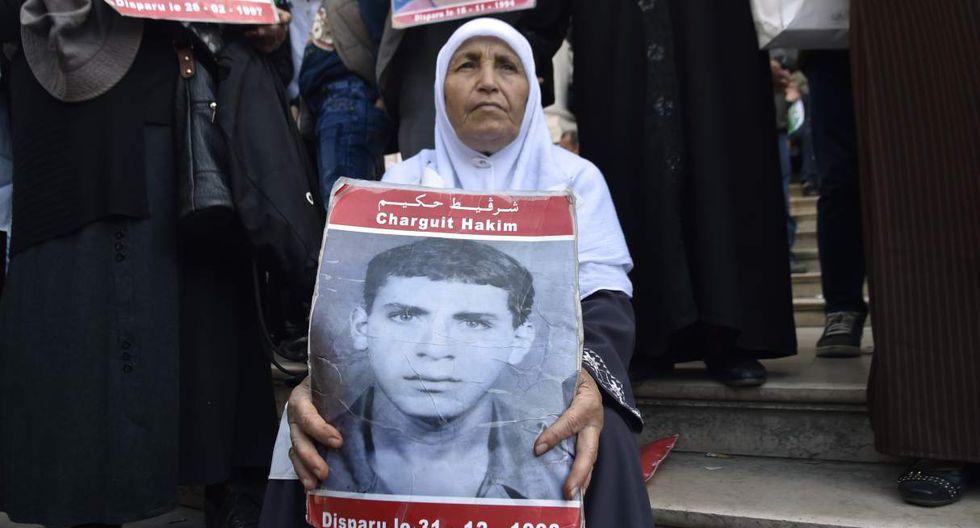 Una mujer argelina lleva el retrato de un hombre desaparecido mientras se manifiesta para exigir un cambio radical en todo el sistema político del país, luego de la renuncia del líder enfermo Abdelaziz Bouteflika. (Foto: AFP)