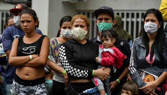 Migrantes venezolanos esperan para abordar un autobús para regresar voluntariamente a su país debido a la pandemia de coronavirus COVID-19, en Cali, Colombia. (AFP / Luis ROBAYO).