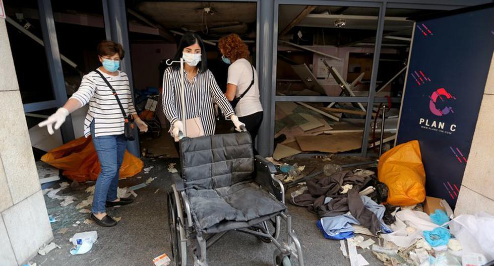 Una mujer busca mover una silla de ruedas por sobre los escombros de un hospital para poder ayudar a un herido. (REUTERS/Mohamed Azakir)