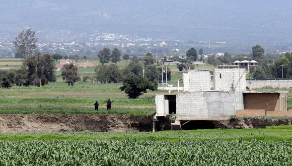 Policías vigilan la zona del socavón de Santa María Zacatepec en Puebla (México). (EFE/Hilda Ríos).
