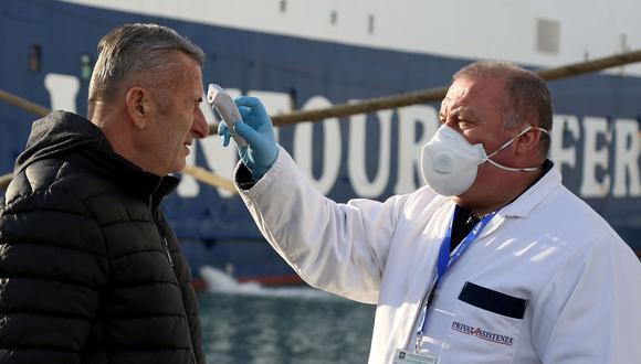 Personal médico revisa a los pasajeros que llegan a Italia para detectar cualquier posible síntoma de coronavirus. (AFP / Gent SHKULLAKU).