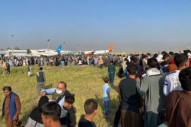 Afghans crowd the airport as they wait to leave Kabul on August 16, 2021.