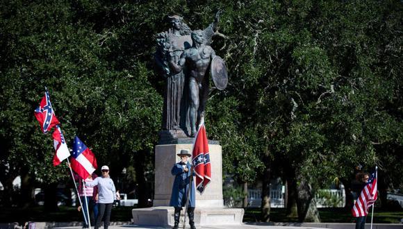 """Braxton Spivey sostiene una bandera de batalla confederada vestido con un uniforme del ejército confederado durante una protesta a favor de la bandera confederada por un grupo llamado """"Banderas del Sur"""" frente a la estatua de los Defensores Confederados de Charleston. (Foto: LOGAN CYRUS / AFP)"""