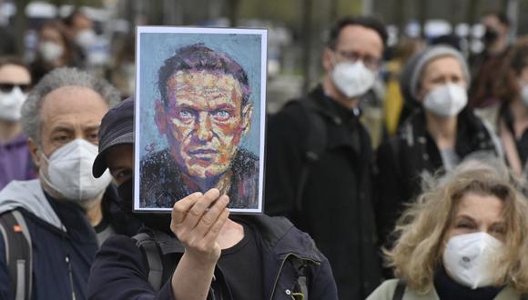 Un manifestante muestra un retrato del crítico del Kremlin Alexei Navalny durante una protesta en su apoyo frente a la cancillería en Berlín, Alemania, el 21 de abril de 2021. (John MACDOUGALL / AFP).