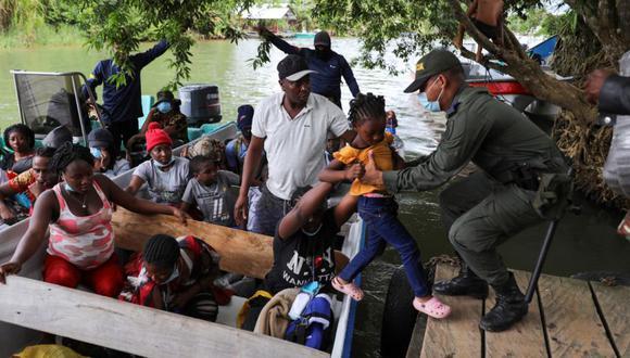 Un niño que viaja con migrantes, en su mayoría haitianos, es ayudado a salir de un bote después de llegar a Acandí para cruzar a Panamá y continuar hacia el norte, en Acandí, Colombia. (Foto: REUTERS / Luisa González).