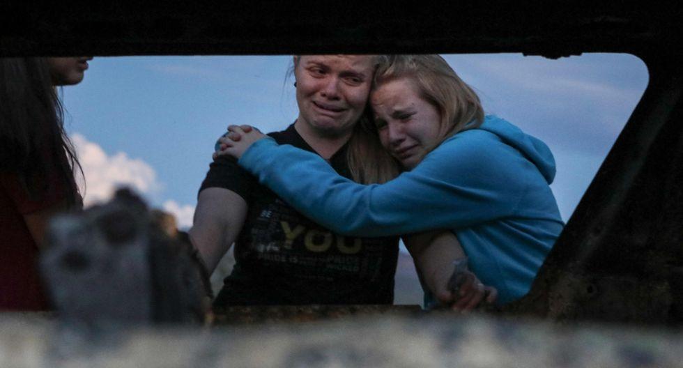 Miembros de la familia Lebaron lloran mientras miran el auto quemado donde se produjo la masacre. Foto: AFP