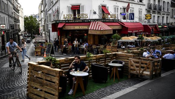 La gente toma unas copas en la terraza ampliada de un café en París el 23 de julio de 2020, en medio de la pandemia del coronavirus COVID-19. (Foto de Christophe ARCHAMBAULT / AFP).