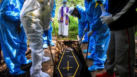 Un pastor acompaña el funeral de una víctima del coronavirus Covid-19 en un cementerio en Pune, India. (Foto de INDRANIL MUKHERJEE / AFP).