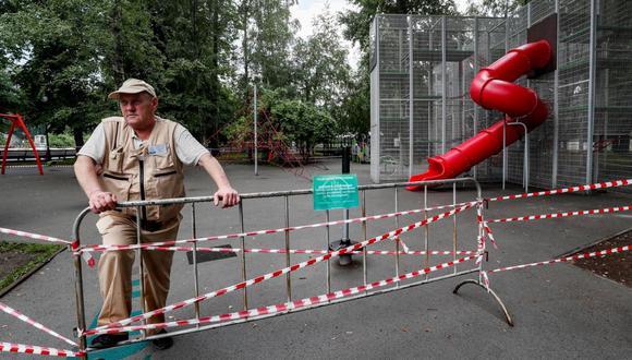 Un guardia de seguridad está de servicio cerca de un parque cerrado en Moscú, Rusia, 15 de junio de 2021. Por decreto del alcalde Sergei Sobyanin, los espacios para niños y deportes de la ciudad fueron cerrados por la pandemia de coronavirus. (EFE / EPA / YURI KOCHETKOV).