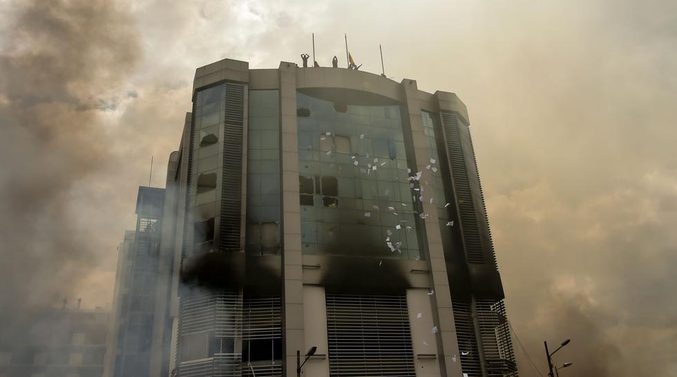 Manifestantes queman y saquean el edifico de la Contraloría en Quito, la capital de Ecuador. (AFP / RODRIGO BUENDIA).
