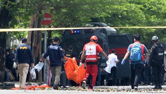 Policías forenses llevan una bolsa para cadáveres frente a la Catedral del Sagrado Corazón de Jesús tras una explosión, en Makassar, Indonesia,el  28 de marzo de 2021. (EFE / EPA / IQBAL LUBIS).