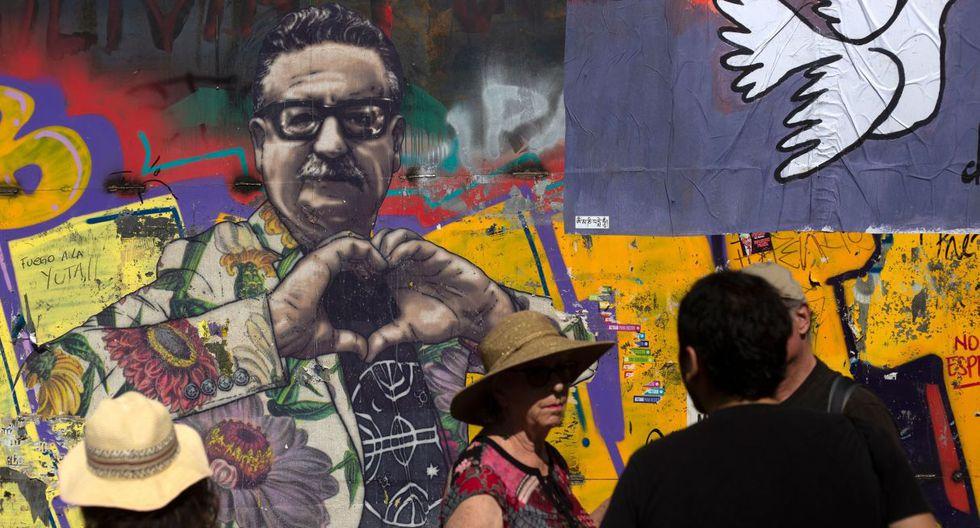 Los turistas permanecen junto a una pared con un mural del ex presidente Salvador Allende en Santiago. (Foto: AFP)