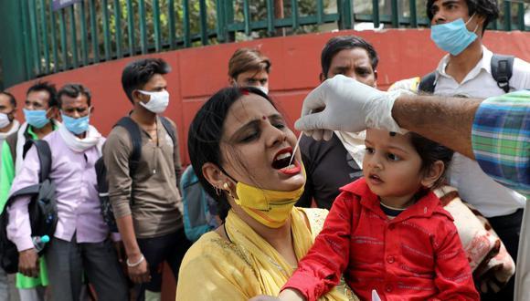 Un trabajador de la salud toma una muestra de un hisopo de una mujer en medio de la propagación de la enfermedad del coronavirus (COVID-19), en una estación de autobuses, en Nueva Delhi, India, el 16 de marzo de 2021. (REUTERS/Anushree Fadnavis).