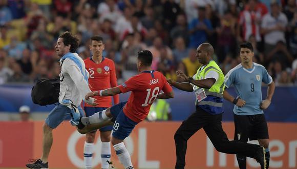 El puntapié de Jara al hincha argentino que invadió la cancha durante Chile - Uruguay. (Foto: AFP)