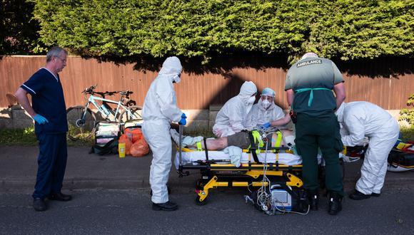 Paramédicos trabajan para estabilizar a un paciente con posibles síntomas de coronavirus COVID-19 en Botley, cerca de Southampton, en el sur de Inglaterra, el 6 de mayo de 2020. (Foto de Leon Neal / POOL / AFP).