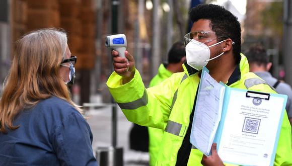 Un funcionario de salud controla la temperatura de un residente en un centro de vacunación de COVID-19 en Sydney, Australia el 27 de julio de 2021 (Foto de archivo: Saeed Khan/ AFP).