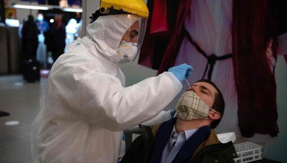 Un trabajador de salud recolecta una muestra de hisopo nasal de un pasajero para analizar COVID-19 antes de que se le permita abordar un ferry a Buenos Aires, en la terminal de la compañía argentina de servicios de ferry Buquebus en el puerto de Montevideo. (AFP/PABLO PORCIUNCULA).