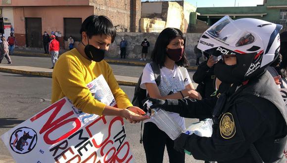 Los manifestantes llegaron con sus carteles a protestar. La policía, por su parte, tuvo el gesto de entregarles mascarillas y desinfectarles las manos para evitar que se contagien del coronavirus. (Foto: Zenaida Condori)