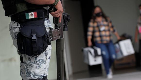 Un miembro de la Guardia Nacional monta guardia mientras un trabajador del Instituto Nacional Electoral (INE) lleva material de votación para ser distribuido a los colegios electorales antes de las elecciones parciales del 6 de junio, en García, en las afueras de Monterrey, México. (REUTERS/Daniel Becerril).