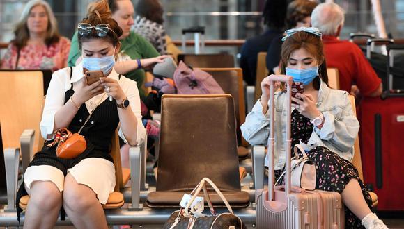 Los viajeros que usan máscaras protectoras en medio de los temores sobre la propagación del nuevo coronavirus COVID-19, esperan en la sala de embarque del Aeropuerto Internacional de Changi, en Singapur. (AFP / Roslan RAHMAN).