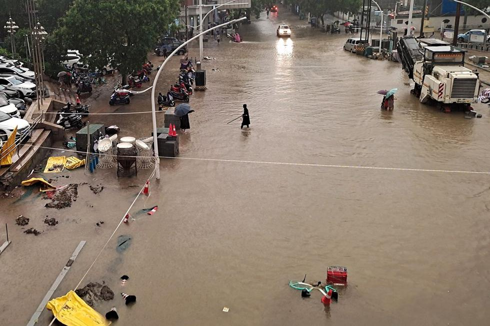 People walking through the floodwaters on Zhengzhou Street.  (Photo STR / AFP).
