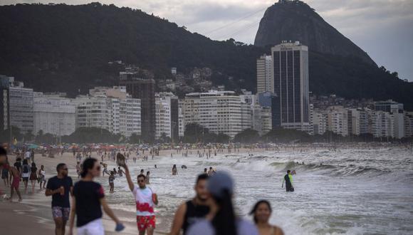 Los bañistas llegan a la playa de Copacabana en medio de la pandemia del coronavirus COVID-19 en Río de Janeiro, Brasil, el 29 de diciembre de 2020. (Foto de MAURO PIMENTEL / AFP).