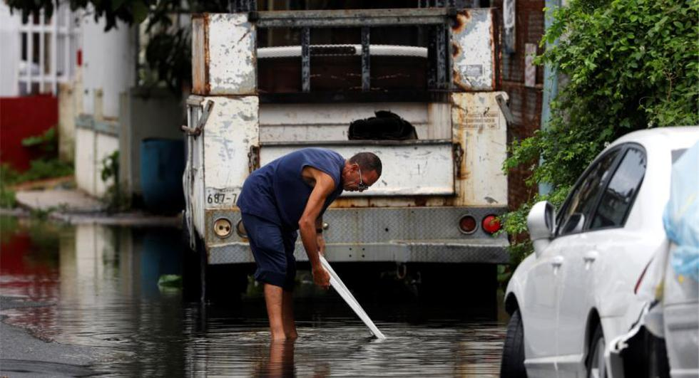 Una persona intenta destapar una alcantarilla tras el paso de la tormenta tropical Isaías, en San Juan (Puerto Rico). (Foto: EFE/ Thais Llorca).