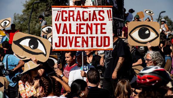 Manifestantes sostienen carteles con ojos en referencia a perdigones de la policía que dejaron ciegos a muchos jóvenes durante las protestas en Chile. (MARTIN BERNETTI / AFP).