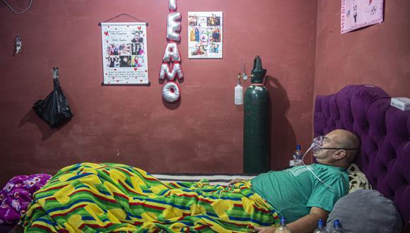 El venezolano Wilmer Hernández, de 44 años, respira ayudado por un tanque de oxígeno en su habitación en el barrio de Villa María del Triunfo, al sur de Lima, el 25 de junio de 2020. Catorce miembros de la familia Hernández llegaron a Perú desde Venezuela hace dos años, pero el el coronavirus ha puesto a prueba sus esperanzas de una vida mejor: el abuelo murió y los otros 13 están tratando de sobrevivir a la enfermedad. (Foto: ERNESTO BENAVIDES / AFP).