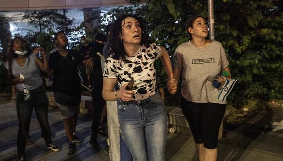 Mujeres israelíes miran la cantidad de misiles que surcan el cielo en la ciudad de Ramla y que fueron lanzados desde Gaza.  (AP Photo/Heidi Levine)