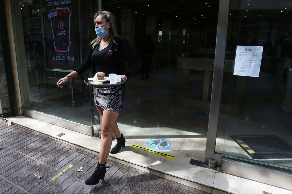"""Una empleada de los llamados """"café con piernas"""" trabaja durante la apertura de los negocios que no son de primera necesidad en el centro de Santiago de Chile. (EFE/Elvis González)."""