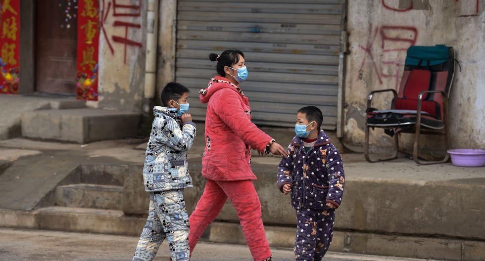 Miembros de una familia con máscaras protectoras son vistos en un vecindario en las afueras de Wuhan. (Foto: AFP)