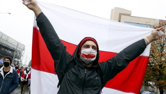 Un hombre porta una antigua bandera blanca-roja-blanca de Bielorrusia durante un mitin para protestar contra los resultados de las elecciones presidenciales que dieron como ganador a Alexander Lukashenko. (Foto: AFP).