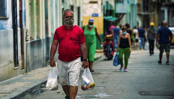 Un cubano con bolsas de la compra camina por una calle de La Habana, el 15 de julio de 2021. (Foto de YAMIL LAGE / AFP).
