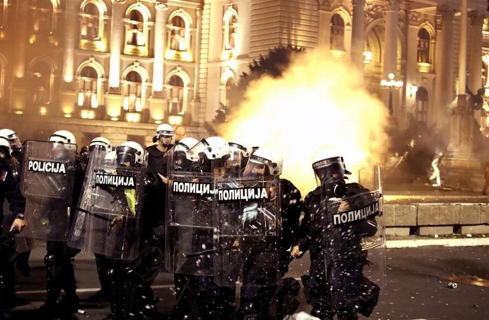 Manifestantes chocan con la policía frente al edificio del Parlamento en Belgrado durante una protesta contra el toque de queda por coronavirus (EFE / EPA / KOCA SULEJMANOVIC).