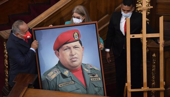 La primera dama Cilia Flores y el líder chavista Diosdado Cabello cargan un retrato del fallecido Hugo Chávez a la Asamblea Nacional de Venezuela. (Foto AP / Matias Delacroix).